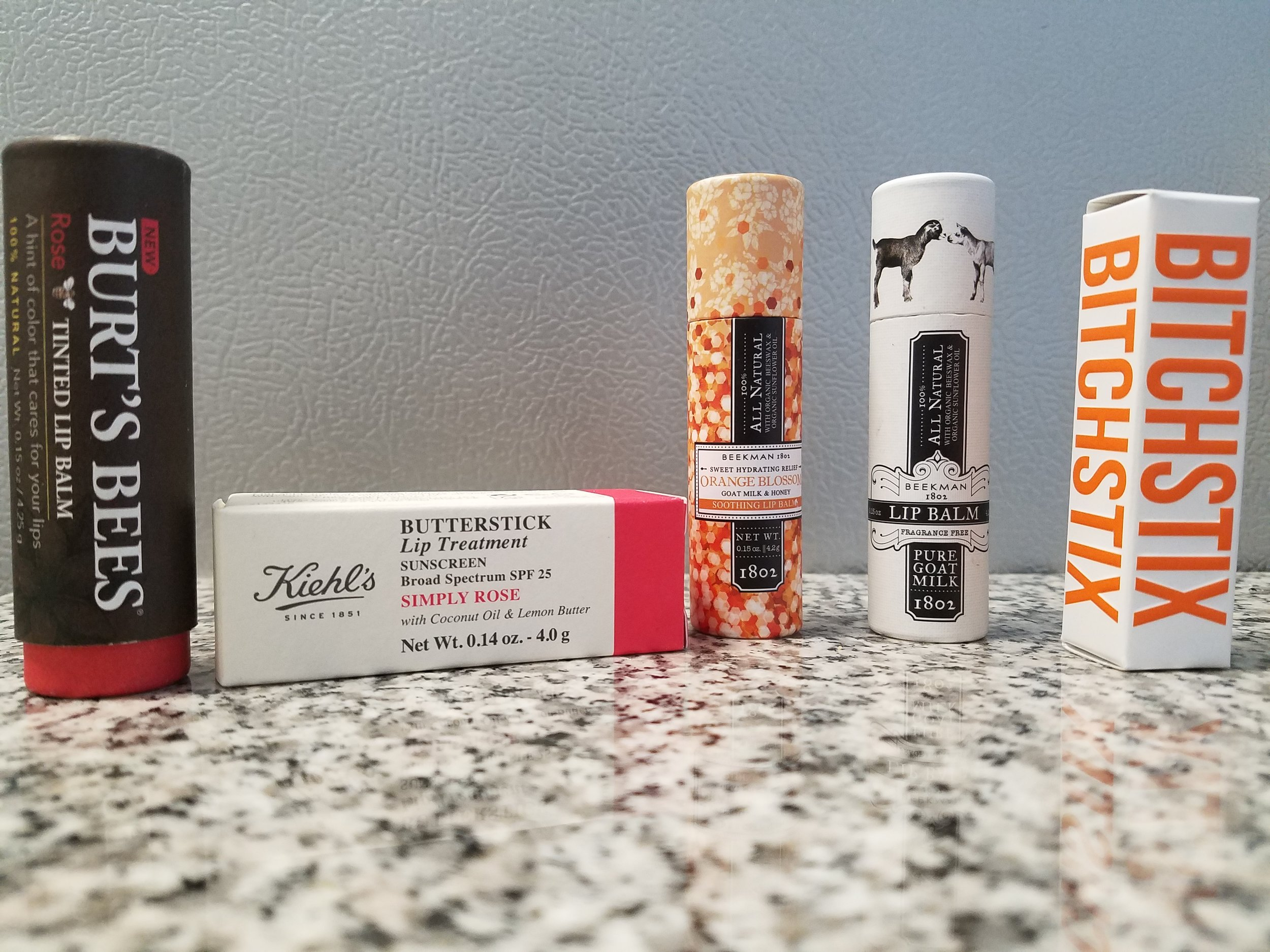 From left to right: Burt's Bees Rose tinted lip balm SPF 25 - Kiehl's Simply Rose butterstick lip treatment - Beekman 1802 All Natural Honey + Orange Blossom and Pure Goat Milk lip balms - Bitch Stix Citrus Orange lip balm SPF 30