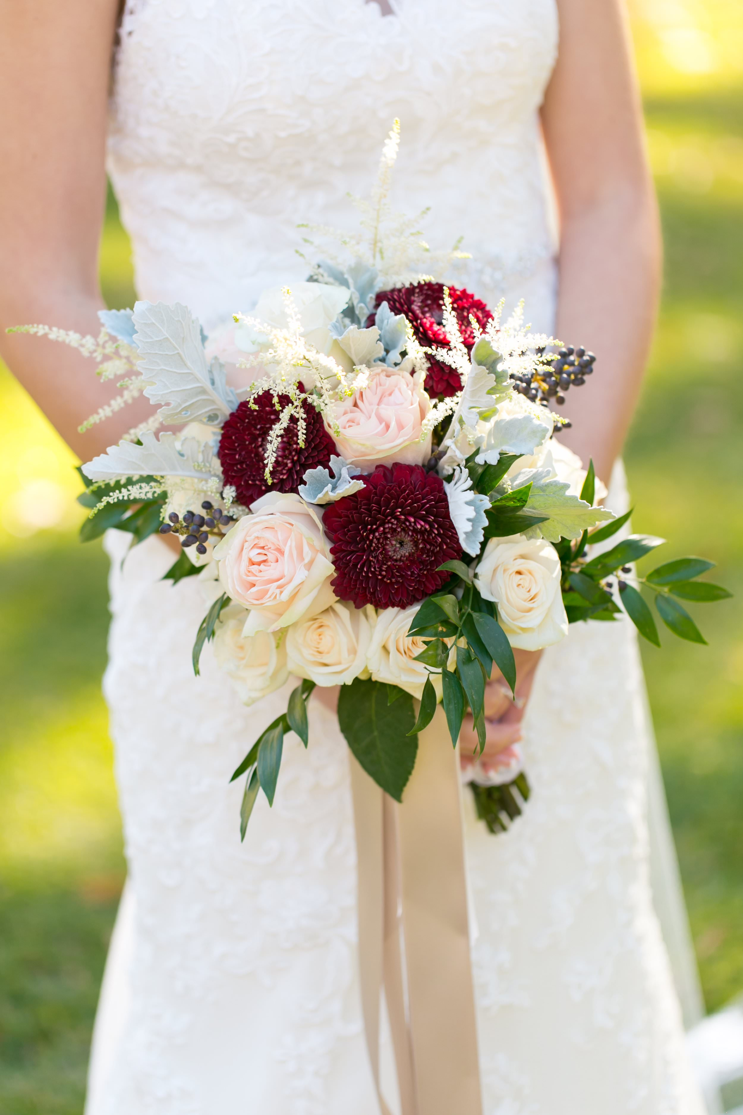 I love the mix of soft gray, cream, and wine colored flowers in Brittany's bridal bouquet by Melissa Senn of  Magnolia House and Garden . It was the ideal palette for her joyful November wedding.