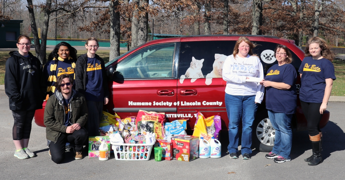 Presenting the donations to Ruth Groce with the Humane Society of Lincoln County are: (left to right) Rhiannon Parkerson; Rosario Lopez; Mary-Elizabeth Gibbons,Psi Beta Secretary; Ross Gates,Psi Beta Treasurer (kneeling); Groce; Jennifer Jenkins,Psi Beta Interim President; and Abbigayle Anderson