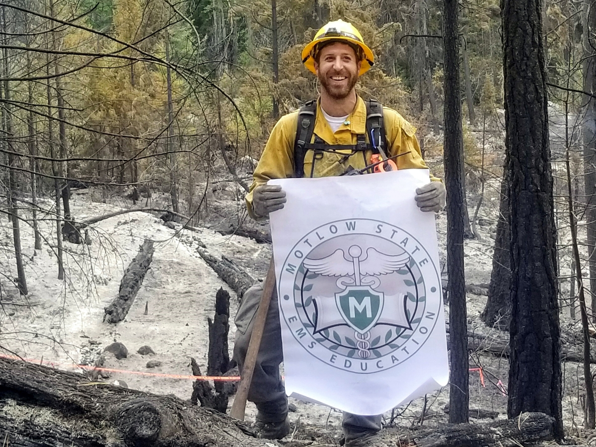 Jared Williams, Motlow State Community College EMS graduate from Smyrna, proudly holds the Motlow EMS Education banner during a break from fighting a wildfire in northern California. Photo provided.