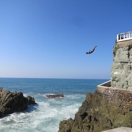 cliff divers - Location: Parque Glorieta Rodolfo Sanchez TaboadaCliff divers jump off into the sea for spectators.