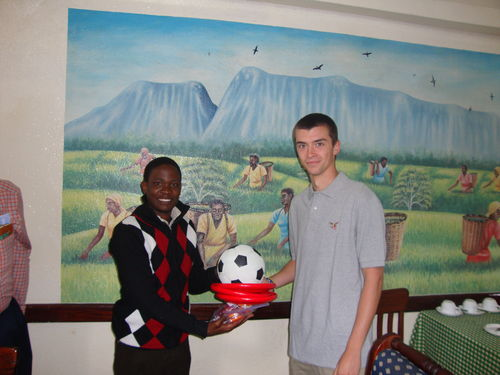 Marcus presents gifts to Vincent Martin for after school program