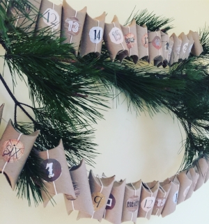 Our Advent Calendar, made of saved tp rolls, numbers printed on reused paper, kitchen twine & a pine branch from the backyard - and filled with bulk bin malt balls.