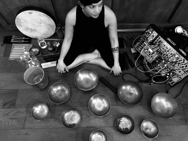 El Larson:heare - El Larson [heare] is a certified sound practitioner who uses ancient Himalayan singing bowls, tuning forks and sound synthesis to help create space for balance and healing. Time as a sound-obsessed yoga hermit equals that involved in underground electronica, where DJing introduced her to manipulating an environment with sound. Years of practicing and giving yoga adjustments in a Mysore Ashtanga room deepened her connection with the frequencies inside the body.