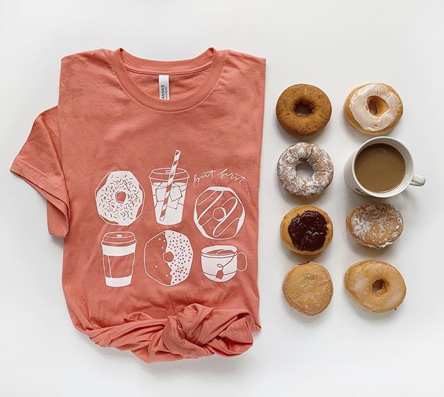 Happy #nationaldonutday! There are plenty of holidays I could do without (basically just the bleak ones without a specific food group dedicated to them) but a day about fried breakfast dessert is at the top of my celebratory snacking list. To properly honor this jubilee, go grab a donut tee for 20% off today! No code necessary because it's too hard to enter a code when you have a Krispy Kreme in each of your donut holders (hands) Find it through the link in my bio. P.S. the first two orders will get a happy little #dunkindonuts surprise inside! *spoiler* it isn't a donut.