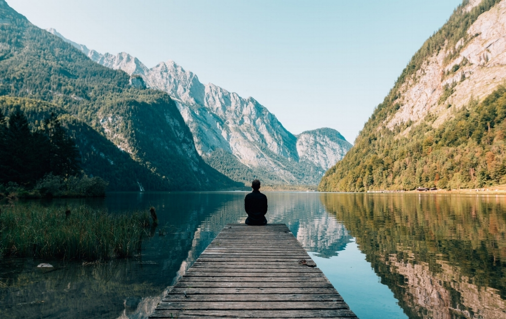 Man sitting on a wooden dock on a lake with mountains reflected in the lake's surface.