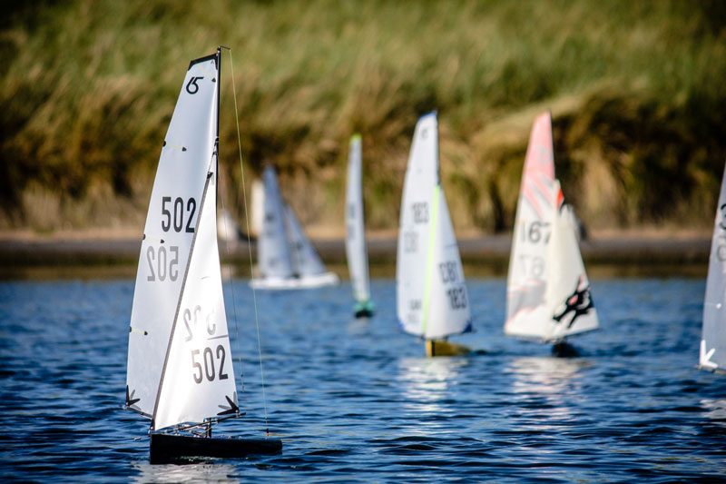 Dragon Force 65 sailboats running a leward leg of a racing course.
