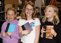 Three young bookmakers hold their finished, colorful hand sewn books.