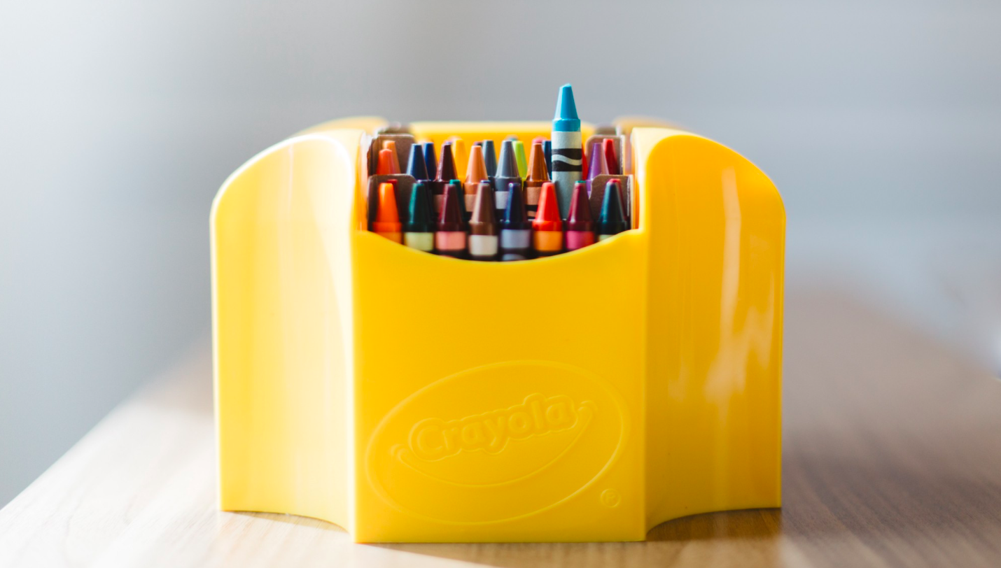 """Yellow box of crayons sit on a wooden table"" by  Evan Kirby"
