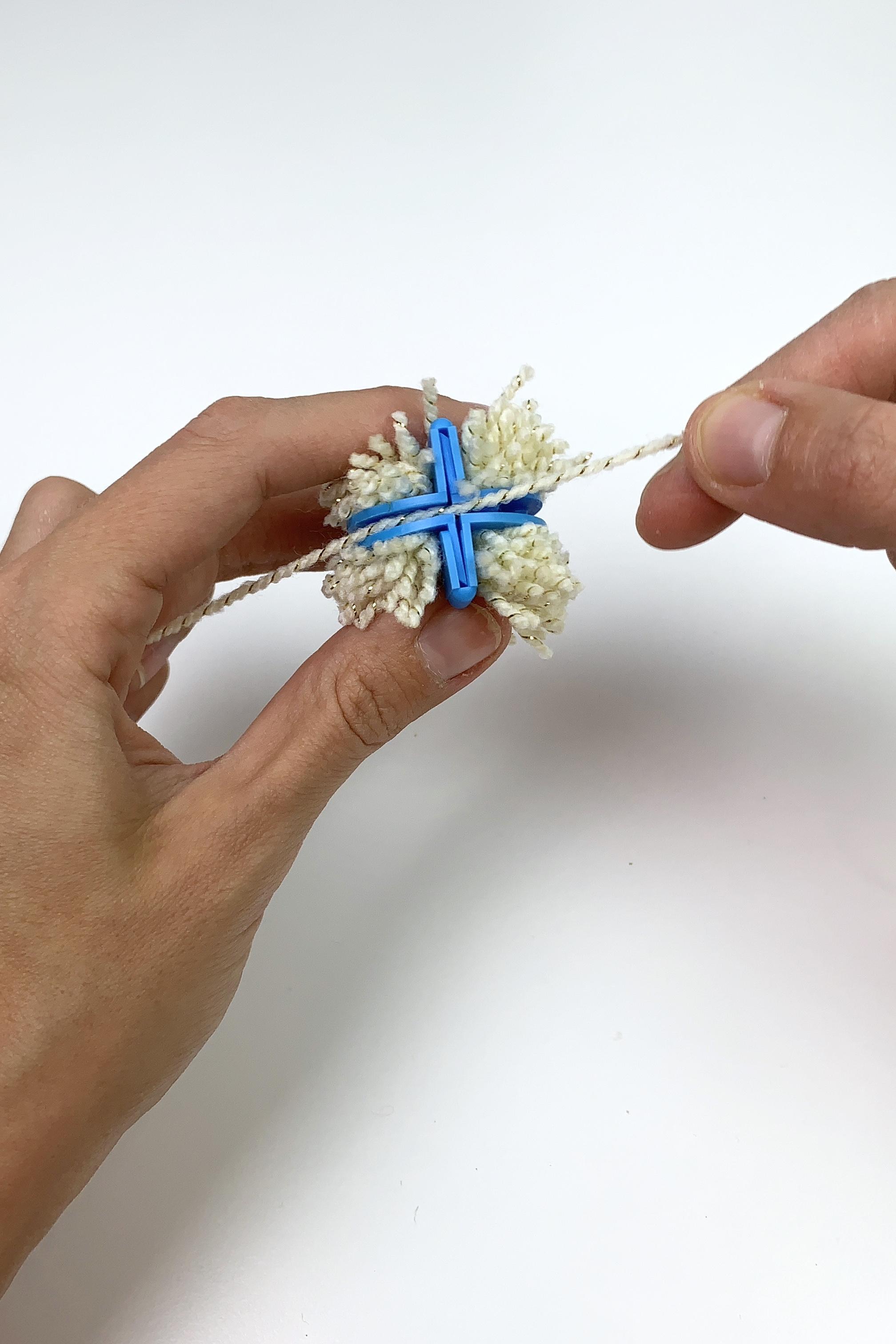 7. - Schneide ein langes Stück von der Wolle ab, führe den Faden an der Seite durch und mache einen Knoten.