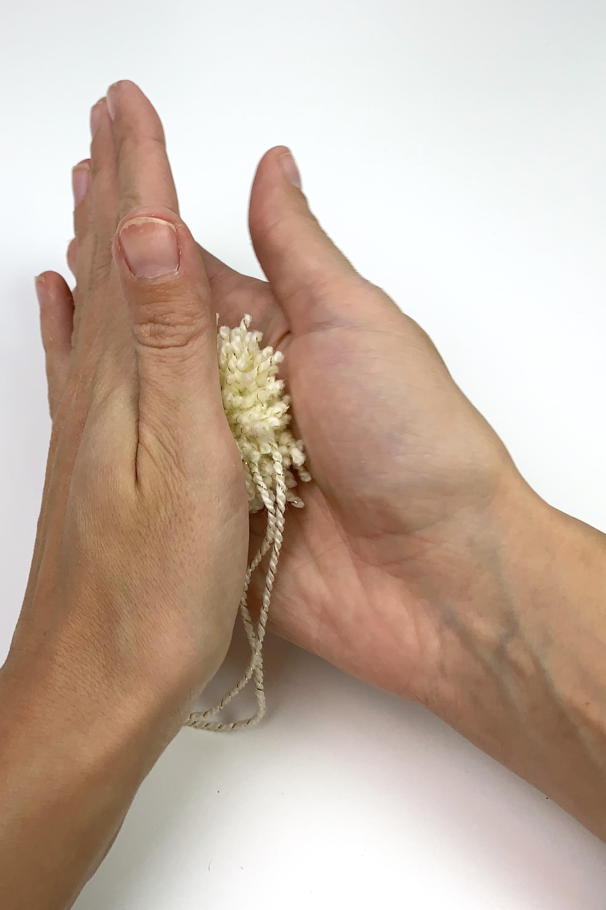 10. - Verreibe den Pompon zwischen deinen Händen. Das ergibt dann eine schöne Form.