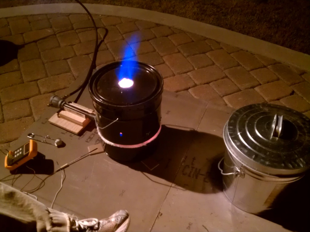 Here is the full setup: Kiln, burner, and burner holder. Not shown is the propane tank and regulator. We set the kiln on top of some old tiles, and then a cement backer board ( Lowes ). We also added a thermocouple (similar to  this ) and digital reader ( Amazon ). We later replaced the galvanized bucket with a cheap stainless pot.