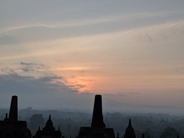 The sun rising over Borobudur, surrounding volcanoes, mountains & community.