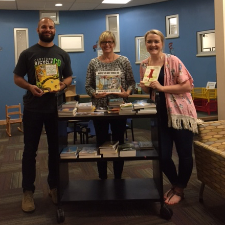 Megan and Adam donating books to Dell Children's Hospital during the Slide UX Goodwill Game.
