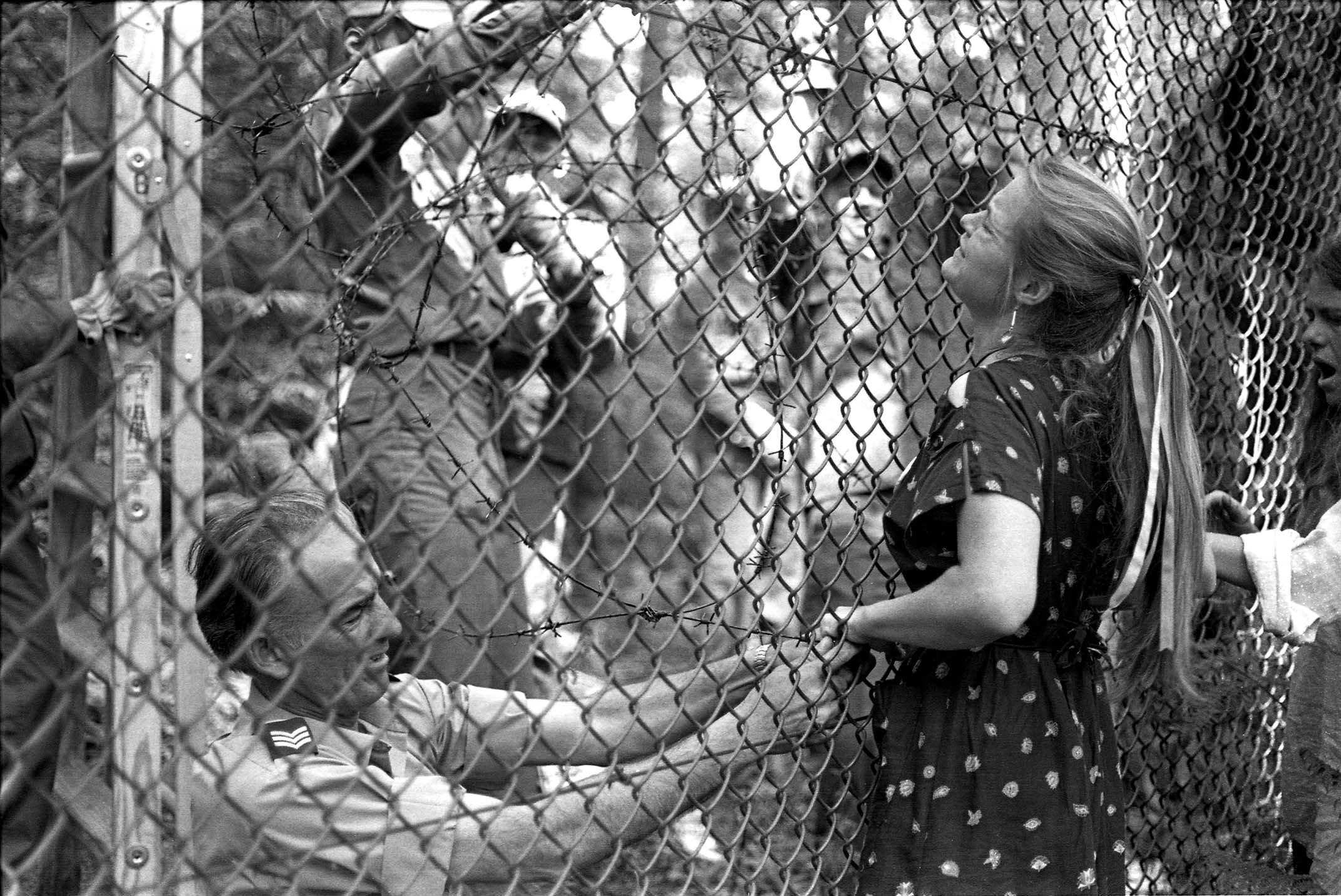 Dr Rebecca Johnson chains herself to the perimeter fence - a peaceful protest method routinely used at Greenham. Photograph by Edward Barber