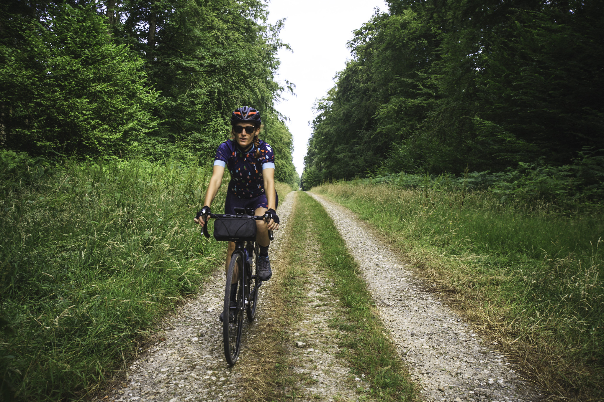 Vanya riding a perfect gravel road through the lush , wild forests of Normandy, France.