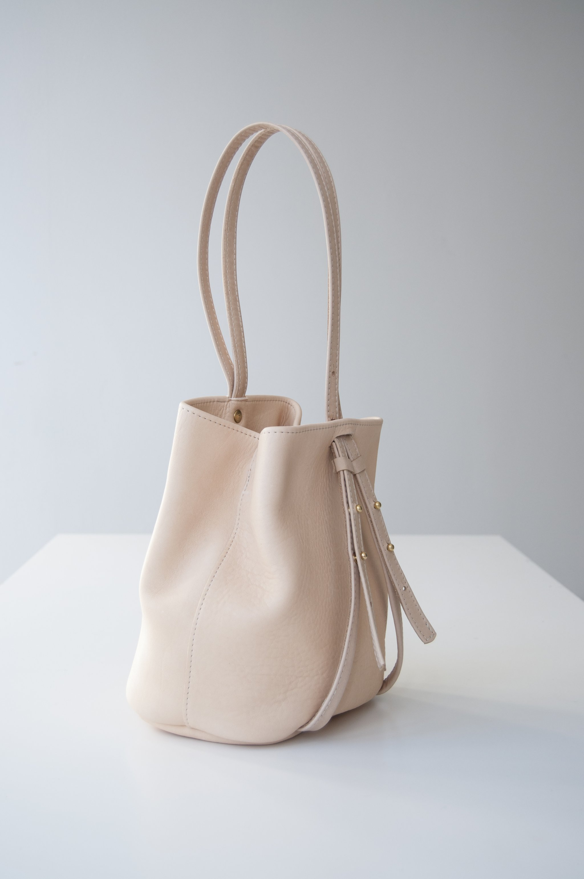 CHC - Small Aura Bucket Bag / Prices VaryThis is the perfect bucket bag to take you anywhere this fall. The leather shifts this silhouette into fall, and all of it is sourced and produced in the United States from sustainable farms. They even dye their leather using vegetable dyes!