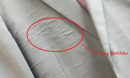 "UNSIGHTLY AND IRREVERSIBLE: ""Fusing bubbles"" on a cheaply made men's suit jacket."