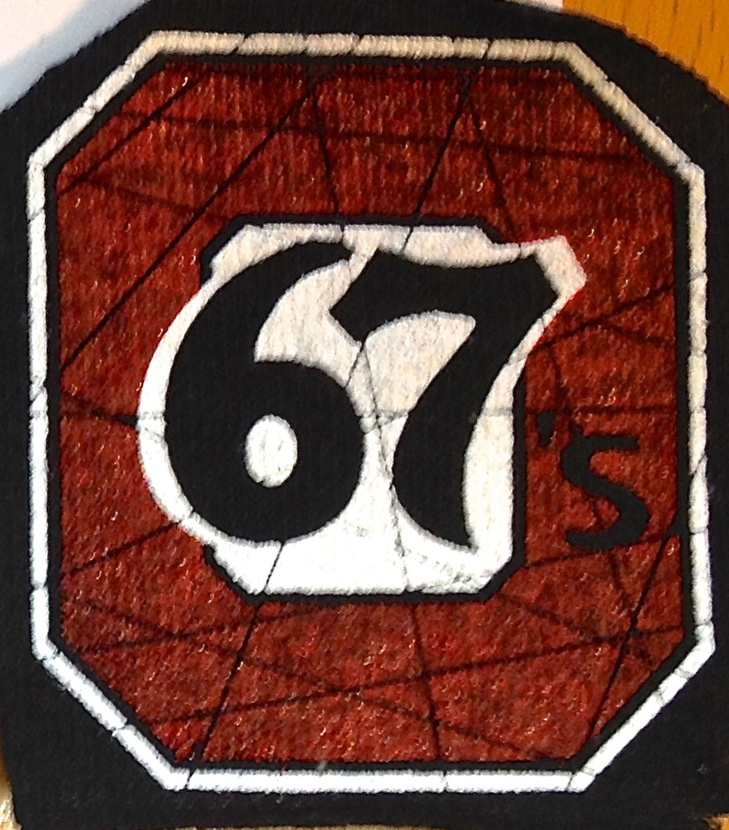 The 67's red is printed directly on the black background.