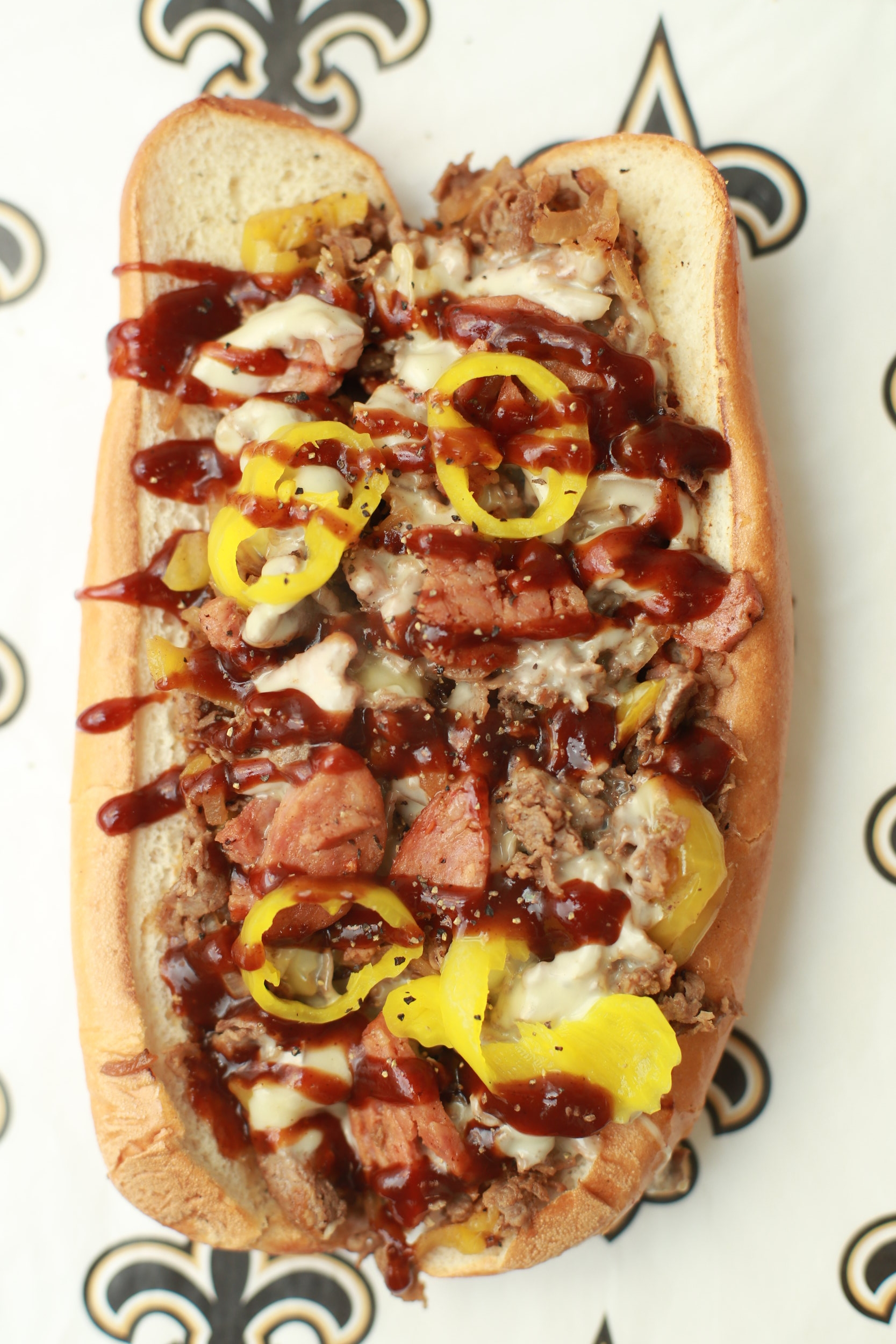 Easy Breesy - Grilled steak, sausage, grilled onions, banana peppers, white American cheese, and topped with BBQ sauceSM. $6.75 / REG. $8.75