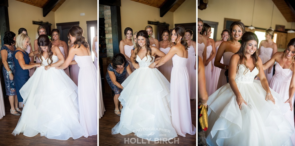bride getting dressed by blush pink bridesmaids