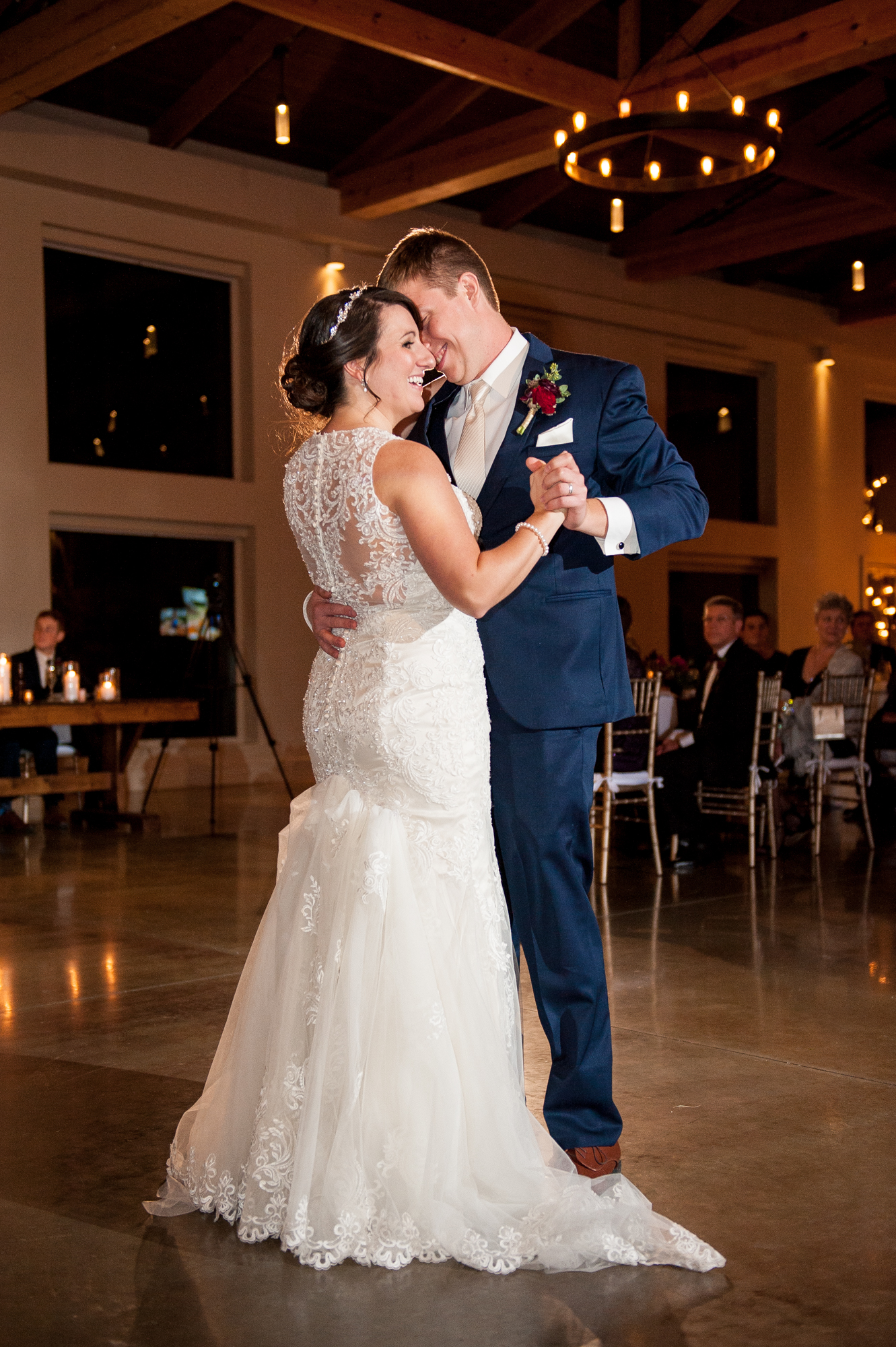 First dance photos are where my off-camera flash (gridded, cross-lighting) really shines.  Again, I don't want to light up the whole room, but I want the bride and groom to be lit well.  This gives me a clear line of sight from the flash to their faces, and again gives me the true color and skin tones on them that I strive for.  One other thing of note on this image - the hair light you see behind their heads was actually a continuous video light from the videographer.  So even with using flash, I can still make use of ambient light, especially uplighting or chandeliers. :)