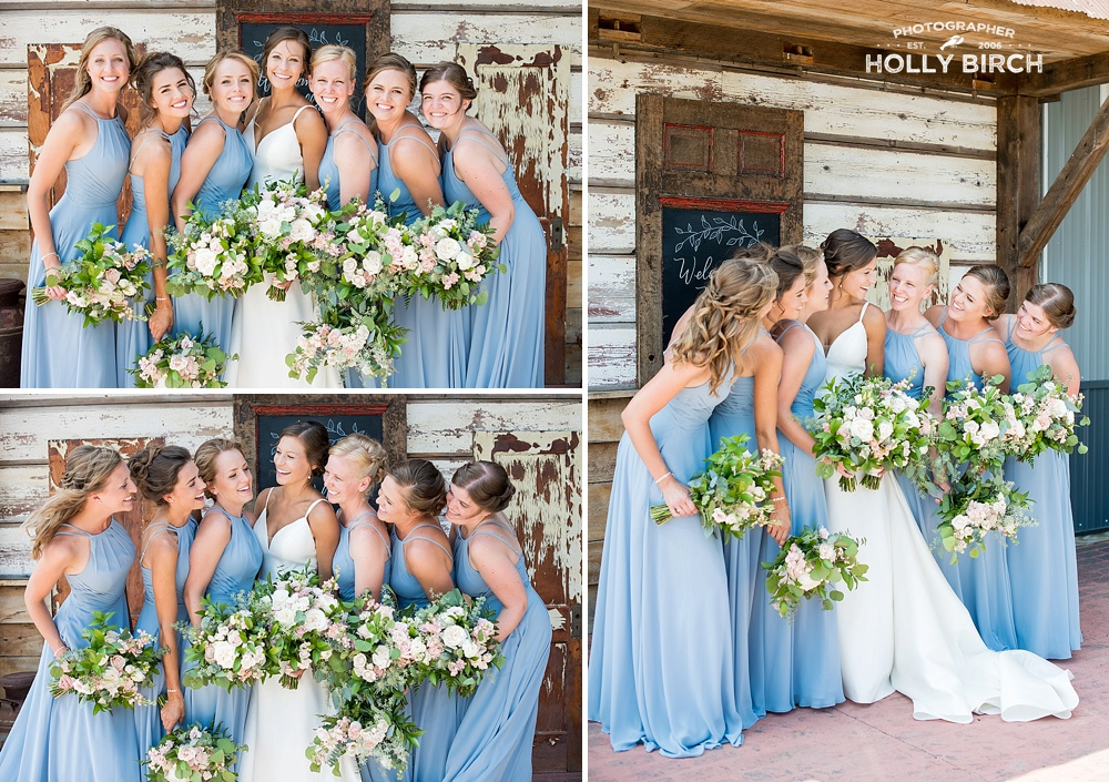 bridesmaids in blue at farm wedding with white and green florals