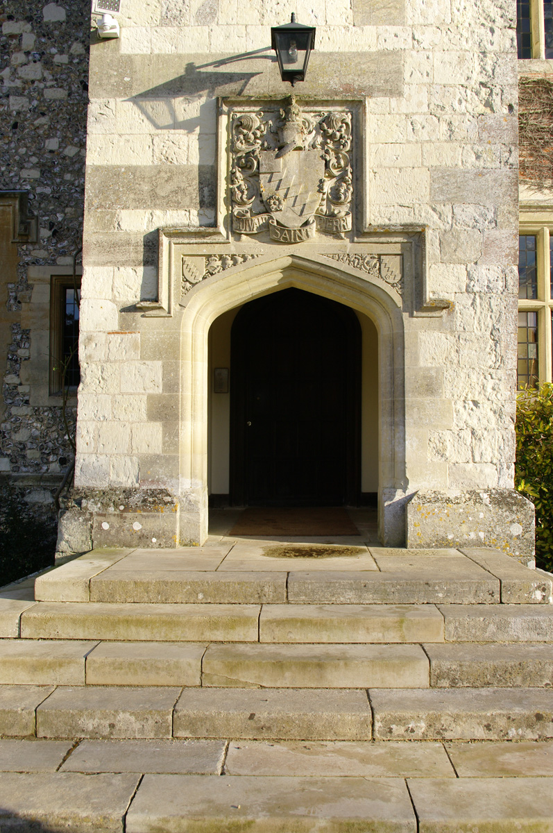 The front entrance of Chawton House, with the Knight family motto and heraldry carved in stone above the front door