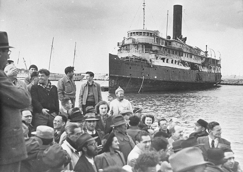 The most famous ship of the Aliyah Bet operation, the Exodus, damaged and docked as a group of Jewish refugees observe. Photo source: Palmach Photo Gallery.