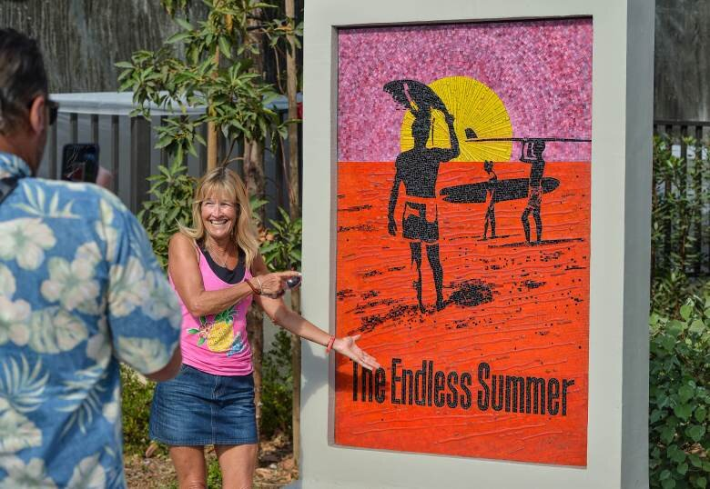 Jeanne Trimm poses with a mosaic of the Endless Summer movie poster at Waterman Plaza in Dana Point, CA, on Thursday, Sep 19, 2019. The city unveiled the mosaic, along with a statue to honor the film's creator, Bruce Brown. The plaza also has memorials to Hobie Alter and Phil Edwards on Pacific Coast Highway. The statues mark Dana Point's continued effort to tap into its rich surf history and culture. (Photo by Jeff Gritchen, Orange County Register/SCNG)