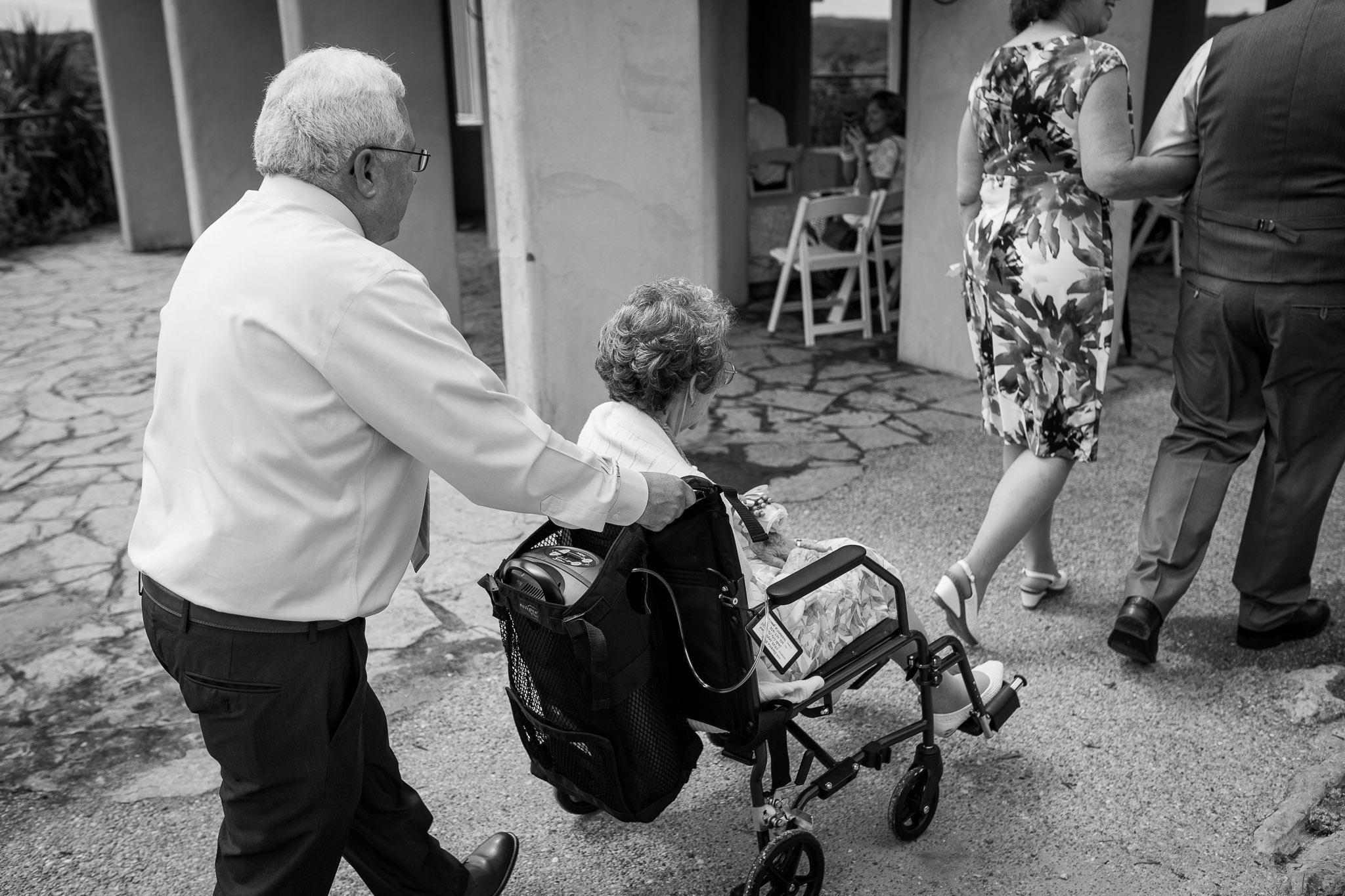 Grooms dad pushing Grandma in wheelchair.