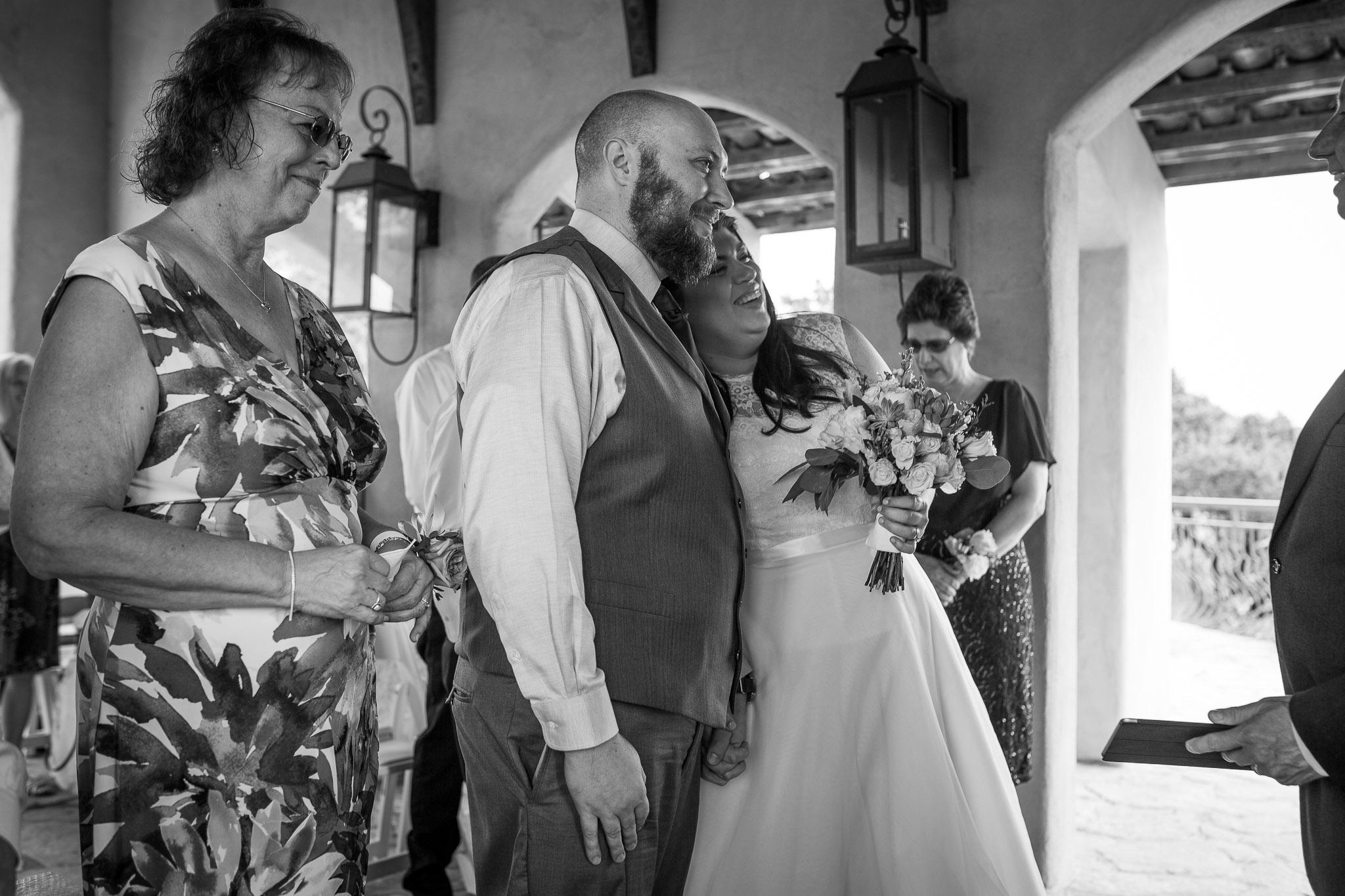 Groom hugging his bride while mom walks down aisle.