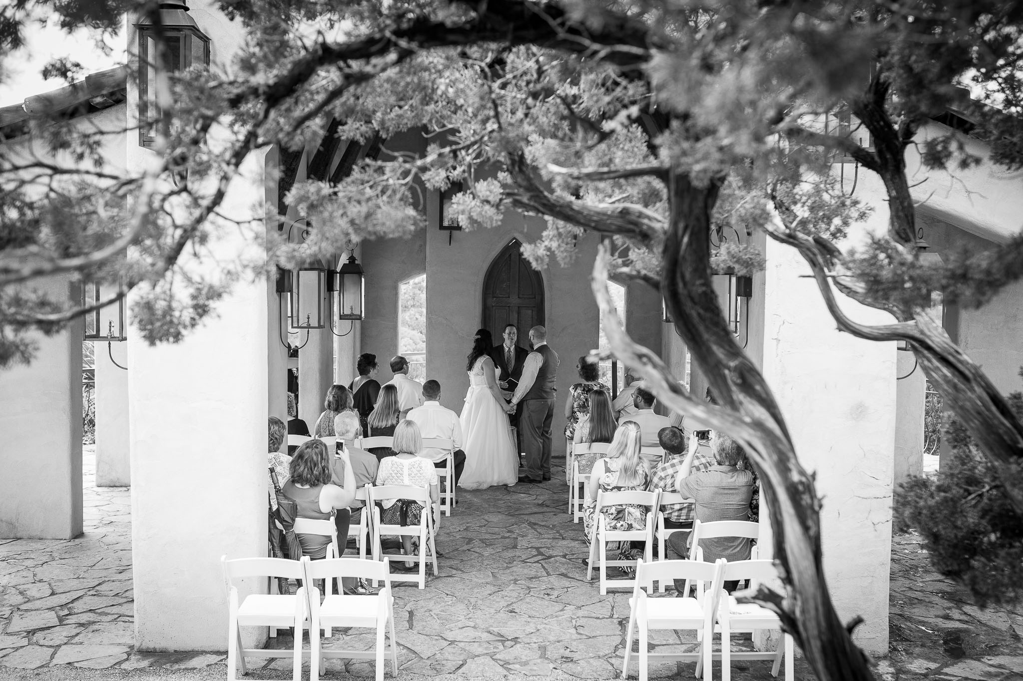 View of bride and groom through trees at wedding ceremony.