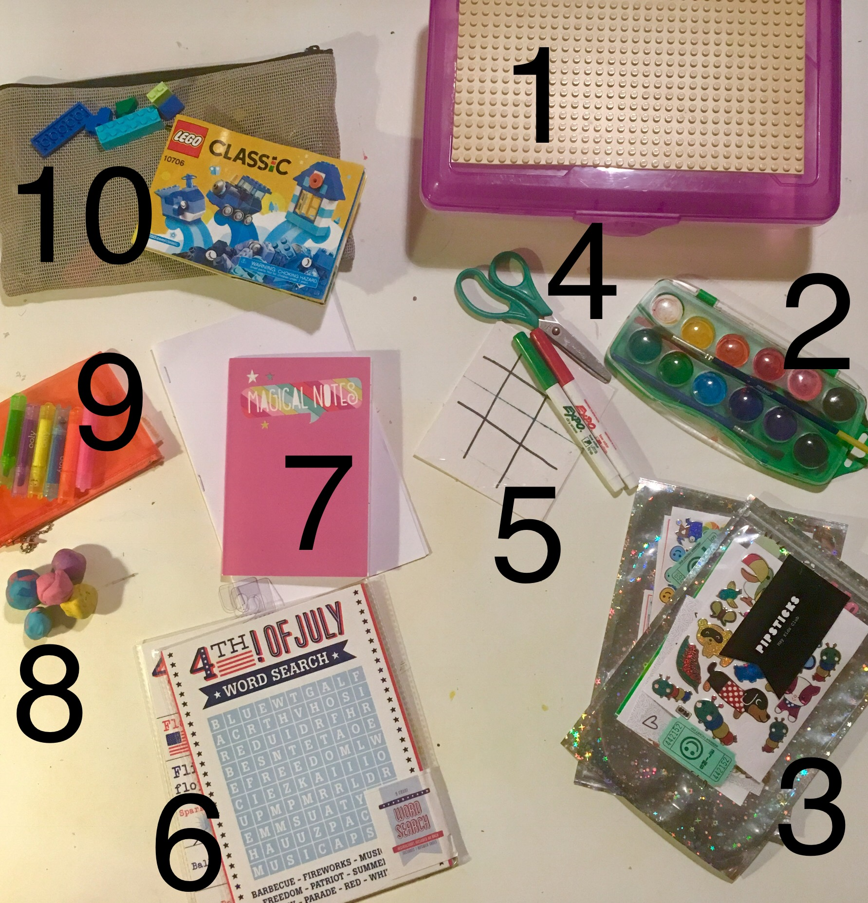 """1.   Plastic snap-lid oversized pencil box   with a piece of   LEGO """"land""""  cut to size and hot glued to top.  2.   Kids pan watercolor set   and brush (all you need is paper, a water cup to wash your brush, and a napkin to dry your brush  3. Stickers! We   subscribe to a monthly sticker club   and it's AWESOME!  4.   Scissors    5.   Dry erase markers   and a homemade double-sided tic tac toe/what we call the """"making squares"""" game...does anyone know the official name?...on a heavy piece of paper wrapped in clear packing tape.  6. Games from the dollar bin...word search, car bingo...  7. A notepad, copy paper folded and stapled into a blank sketchbook, watercolor scrap paper  8.   Modeling clay    9.   Markers   and a soft   carrying pouch    10.   LEGO's   and a   carrying pouch    Optional:    Figurines  , washi tape, pencils, puzzles, a   Spirograph  ...the possibilities are endless...space dependent ;-)"""