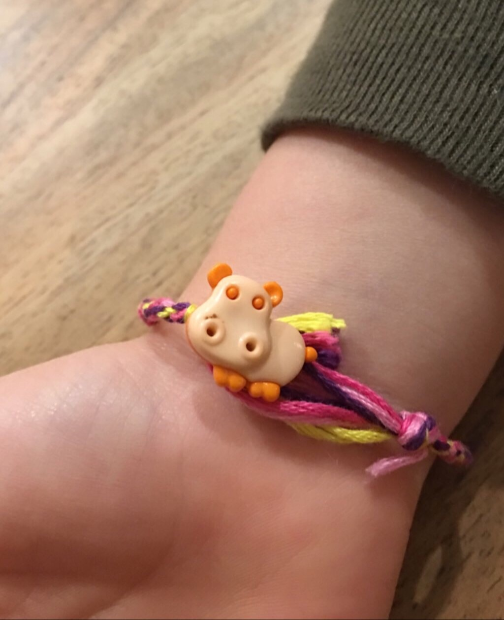 This is a little hippo button with an opening on the reverse that the bracelet was tied to. The slip knot went over the hippo and is adjustable.