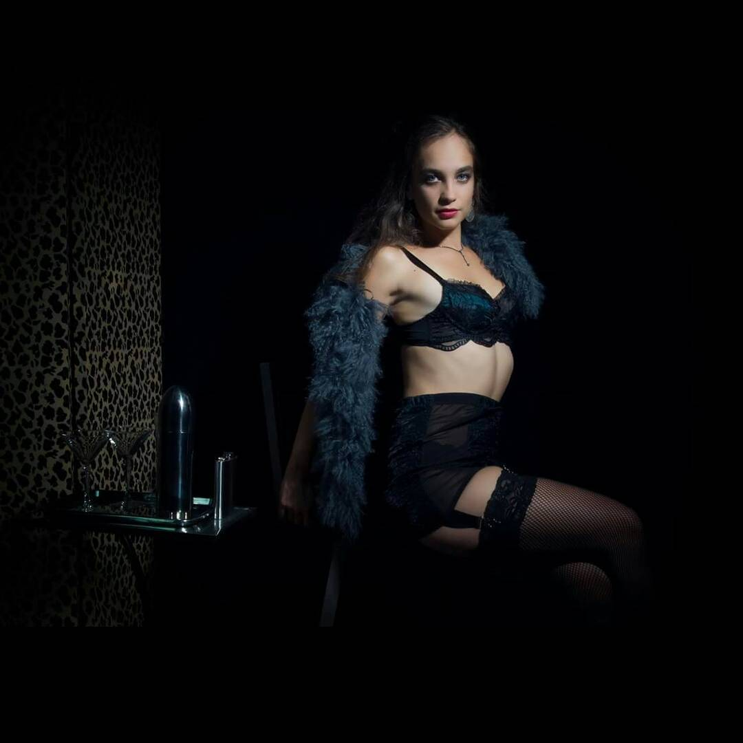 Model wearing dark blue boa and black lingerie with garters from the curated collection of VaVaVooom in Asheville NC.