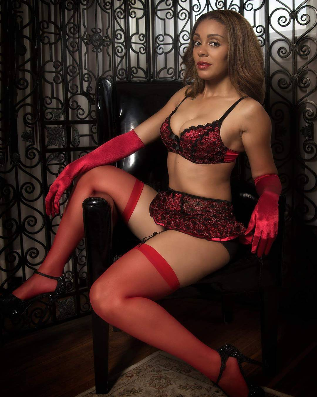 Model wearing red bra and garter skirt set with rid thigh high stockings available from VaVaVooom's selection of lingerie and apparel.