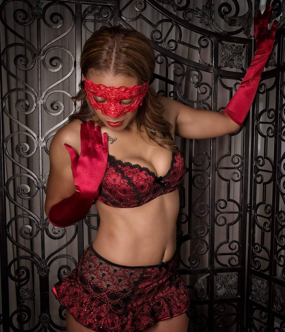 Model wearing lacy eye mask, red bra and garter skirt set with red thigh high stockings available from VaVaVooom's selection of lingerie and apparel.
