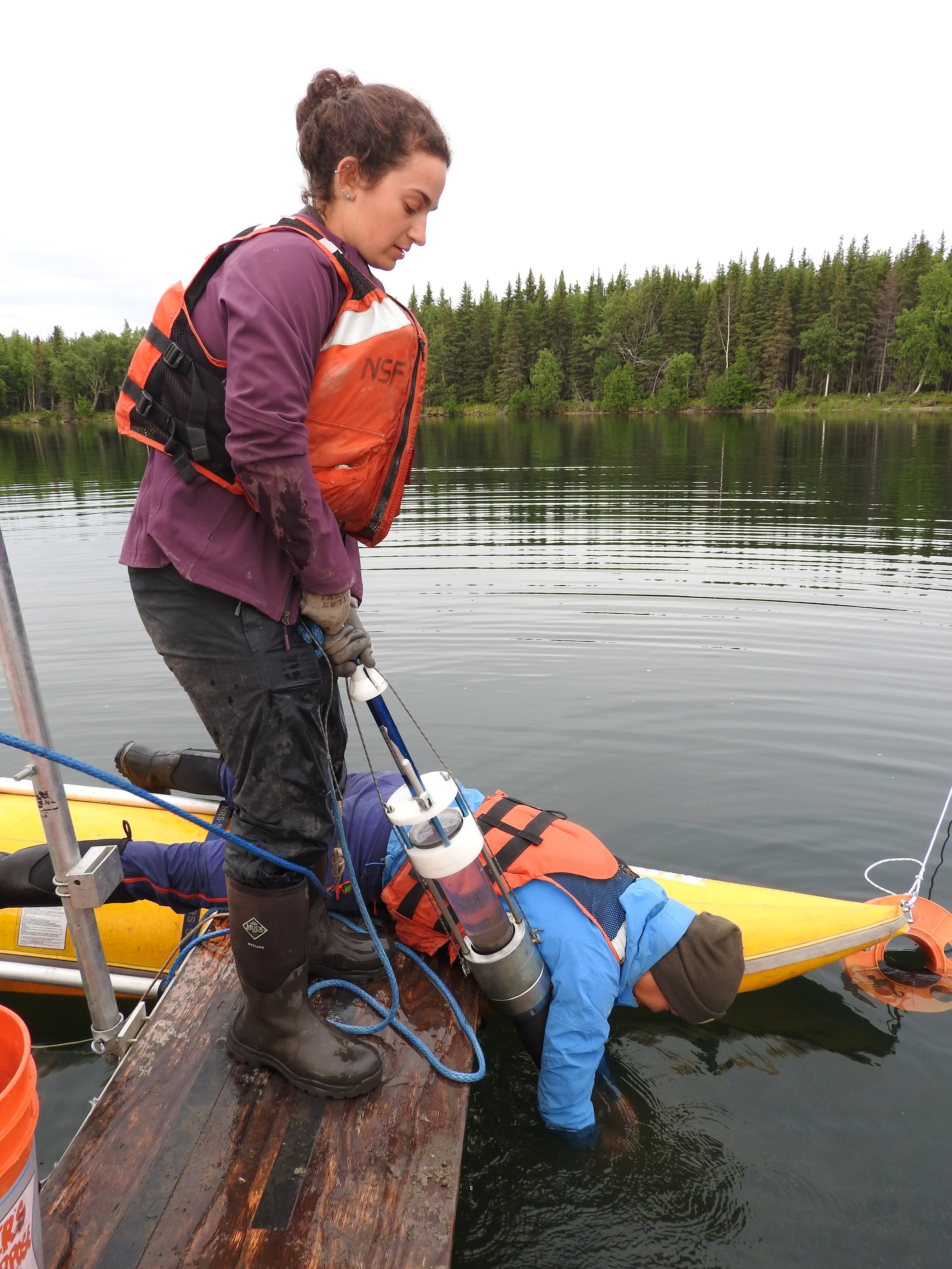 Ellie Broadman and Annie Wong retrieving surface sediments with a Uwitec percussion corer at Kelly Lake