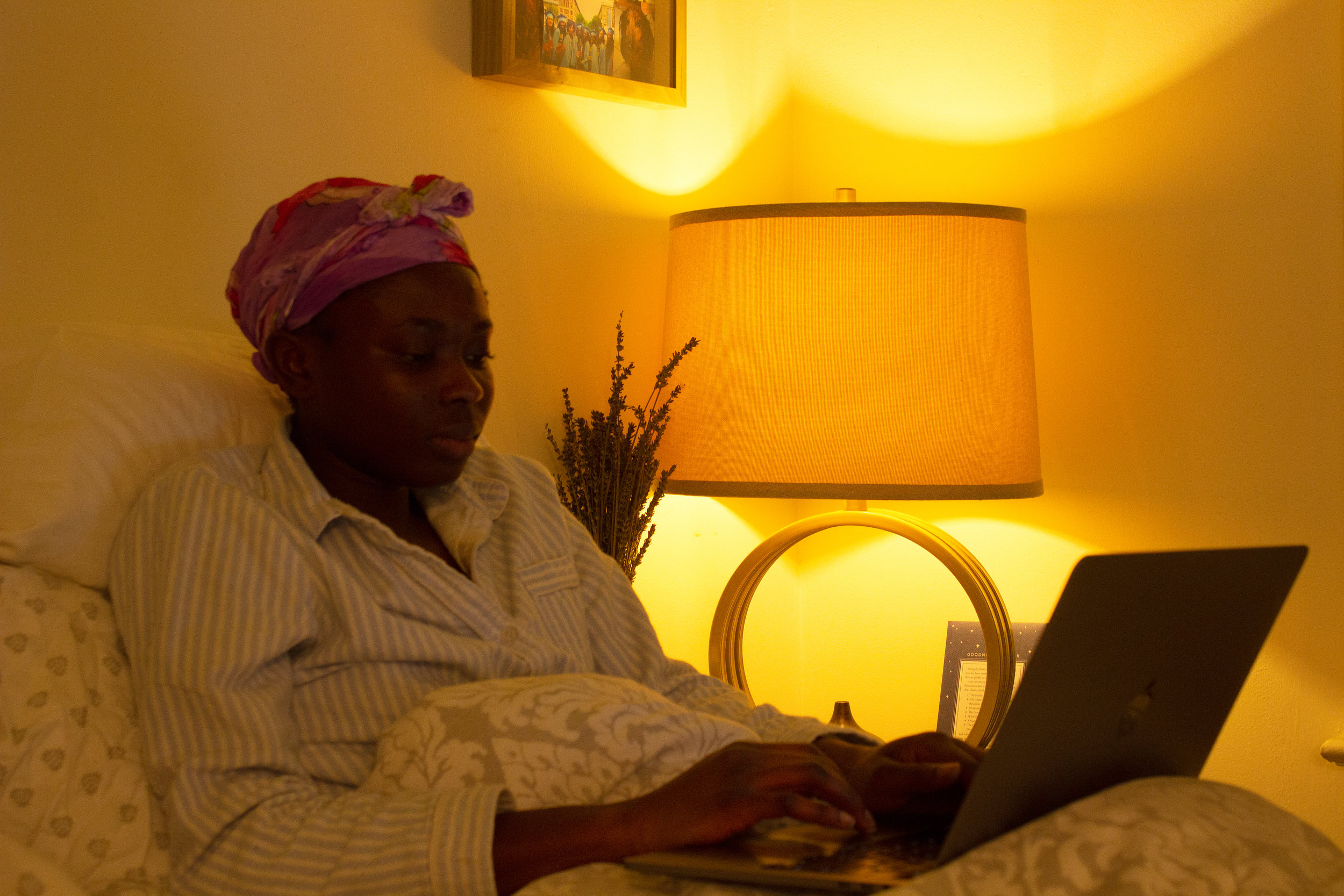 Adefunke Sonaike, 24, finishes a class assignment in her bed before going to sleep.