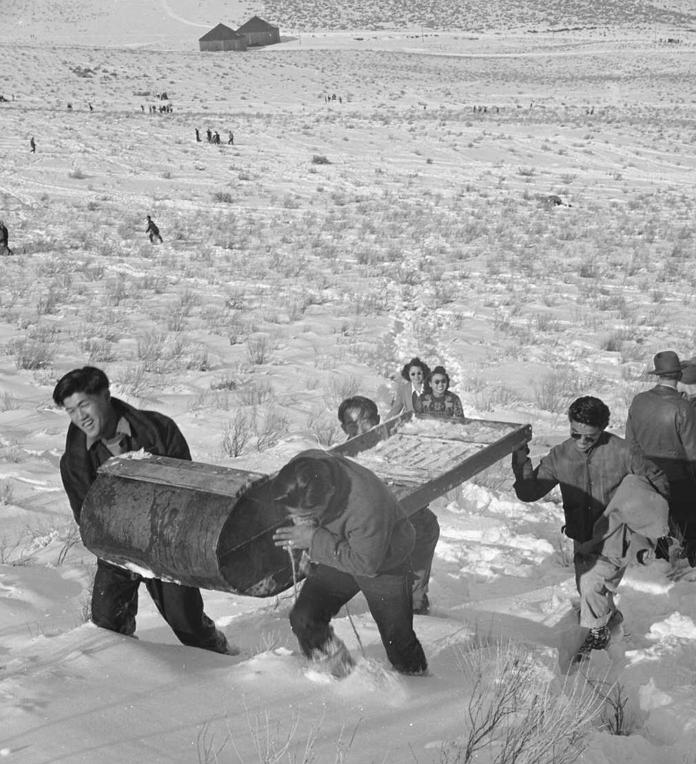 """The original caption for this photograph reads: """"Tule Lake Relocation Center, Newell, California. A pleasant Sunday afternoon's recreation is spent by evacuee winter sports enthusiasts, on the slopes of Castle Mountain. Homemade sleds and various other homemade pieces of equipment were used by these young people."""""""