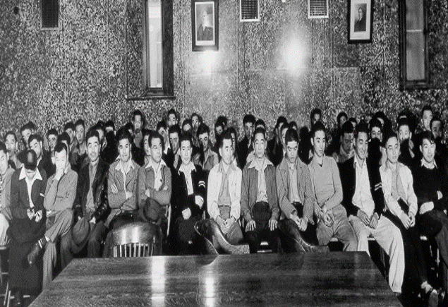 This is a photograph of many of the 63 Nisei draft resisters from the Heart Mountain Relocation Center on the first day of their mass trial for draft resistance in a federal courtroom in Cheyenne, Wyoming, in 1944.