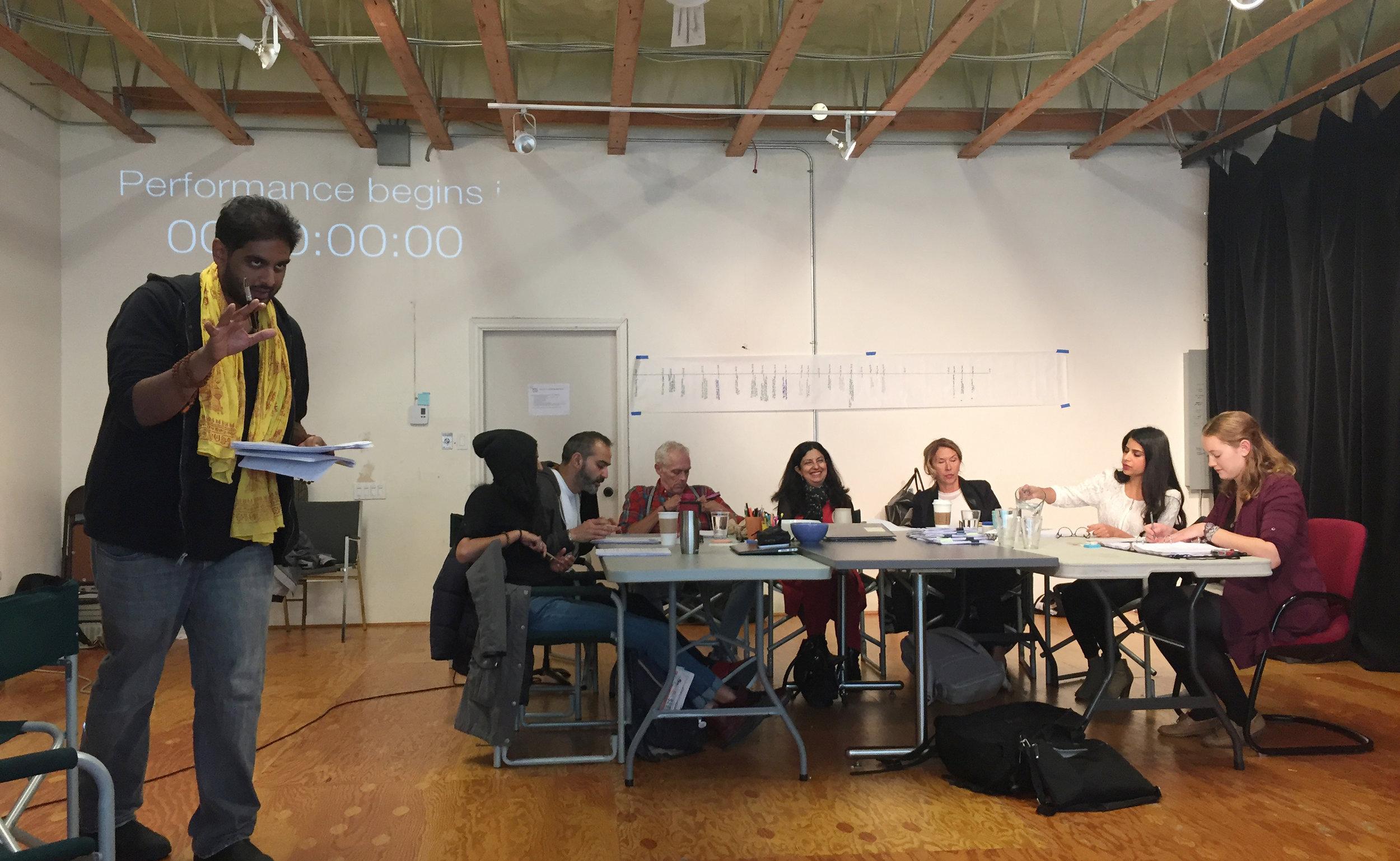 (L to R: Director Jiv Parasram speaks to audience at workshop reading of  Victim Impact . Outreach Coordinator Gavan Cheema, performers Munish Sharma, Allan Morgan, Nimet Kanji, Jenn Griffin and Risha Nanda, and stage manager Heidi Quicke. Photo: Belinda Bruce)