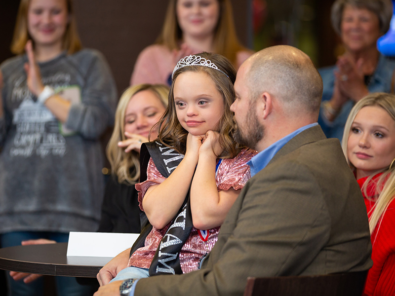 Brad Armstrong holds Aubrey during her Children's Miracle Network Hospitals Champion celebration while their family and friends observe.