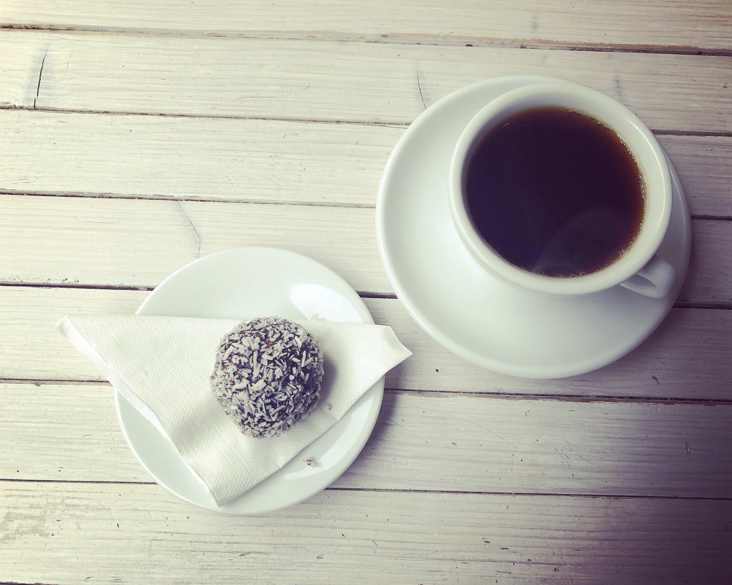 Black coffee and chokladbollar at  Djäkne Coffee Bar  in Malmö
