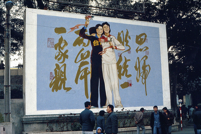 Image: China & Taiwan: 2 sisters, Large propaganda board with China and Taiwan depicted as two sisters, happily holding each other in Xiamen, PRC: 思归照统一,两岸一家亲,  kattebelletje , CC BY-NC 2.0