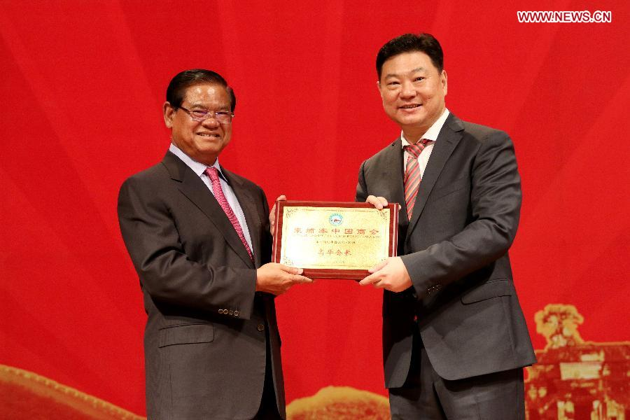 Image: Cambodian Deputy Prime Minister and Interior Minister Sar Kheng (L) hands over a plaque to Gao Hua, re-elected president of the Chinese Chamber of Commerce in Cambodia, in Phnom Penh, Cambodia, July 10, 2015; News.cn