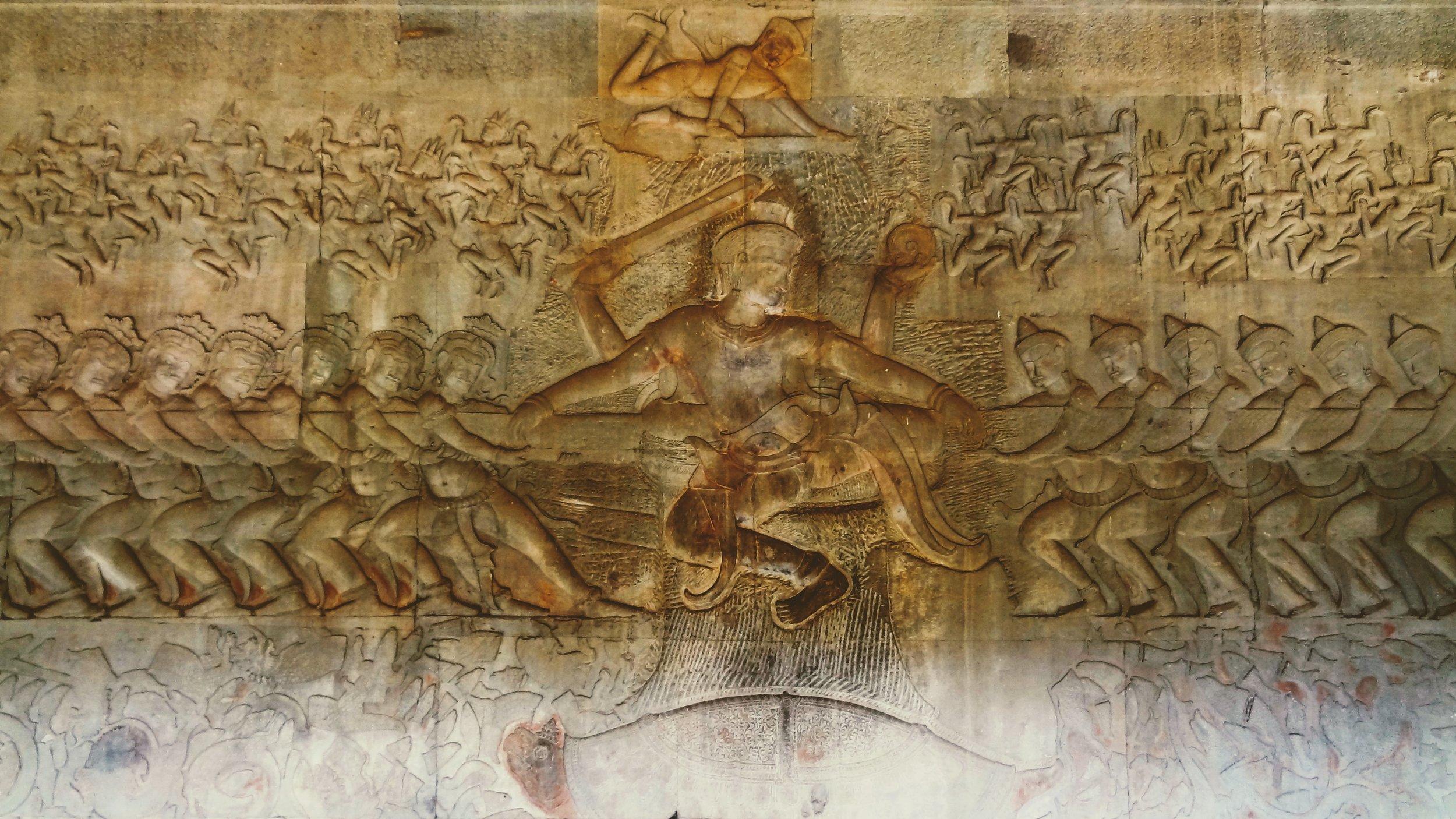 The Churning of the Ocean of Milk (សមុទ្រ មន្ថន) symbolises end of war, strife and the struggle for supremacy, and with it the emergence of the political order, hence the allusion to immortality (អម្រឹត); Image:  Olaf Tausch  (2015), Wikimedia Commons; CC BY 3.0  Description: Wischnu in der Mitte beim Quirlen des Milchmeeres, Südflügel der Ostseite der dritten Galerie des Tempels von Angkor Wat (អង្គរវត្ត 'Tempelstadt), Provinz Siem Reap, Kambodscha
