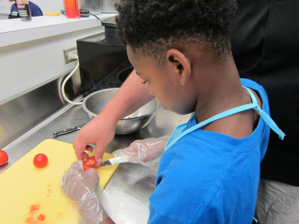 With a little help, a young chef safely slices a tomato. Photo by: John Carlson