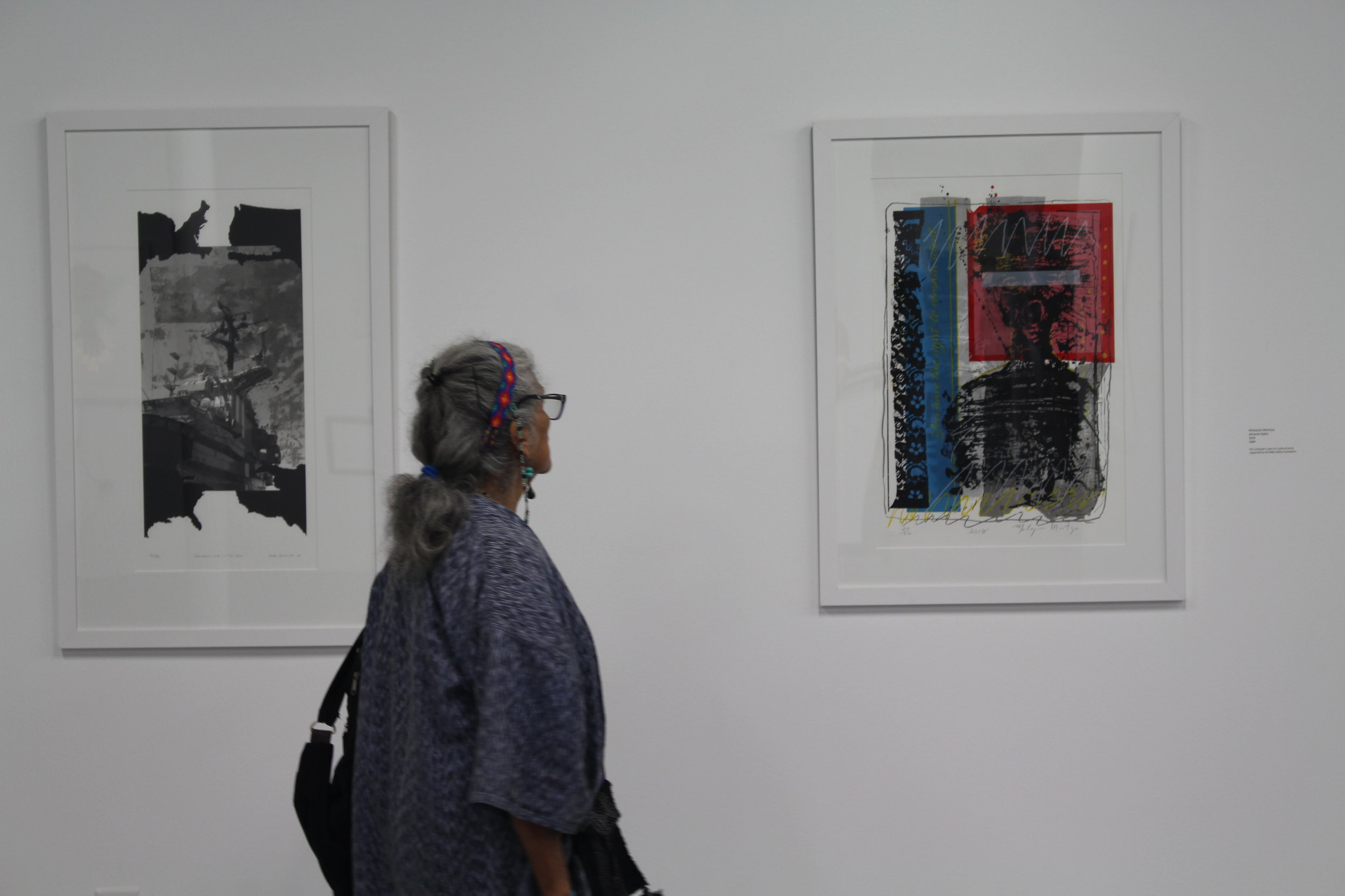 Master Dia de los Muertos Altar Maker and longtime SHG supporter,Ofelia Esparza, takes moment to view  Miranda Rights  at the 45th Annual Print Fair and Exhibition.